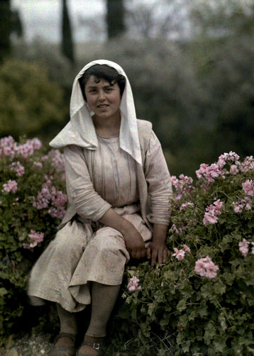 Young woman sitting in a garden of flowers, Corfu
