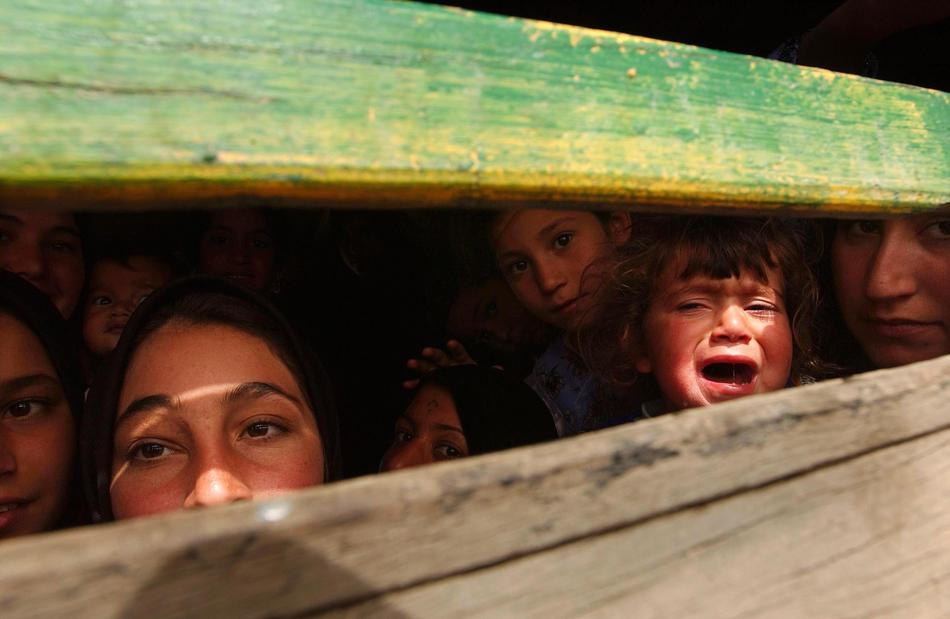 A family tries to leave the besieged Iraqi city of Basra March 31, 2003 in the back of a truck near a British manned bridge that had become a demarcation line. Photo by Spencer Platt/Getty Images.