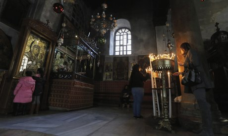 Visitors light candles in the Church of the Nativity.