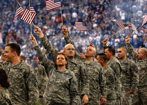 Soldiers wave American flags at the RCA Dome in Indianapolis.  Photo courtesy Staff Sgt. Russell Lee Klika, U.S. Army.