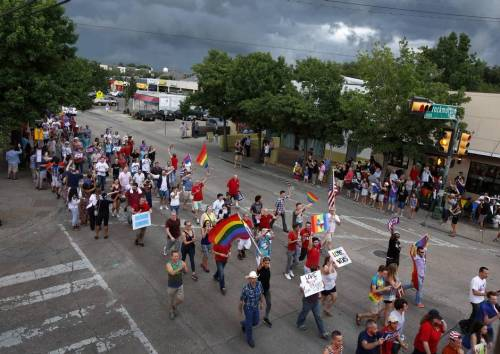 Despite a looming rainstorm, gay couples and their families and friends marched down Cedar Springs Road in Dallas to celebrate the same-sex marriage ruling on Friday, June 26.