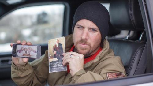 Oregon protestor, Jon Ritzheimer, displays a family picture on his phone and a copy of the Constitution to the media at the Malheur National Wildlife Refuge headquarters.  He needs bottled water and Ramen noodles, too.