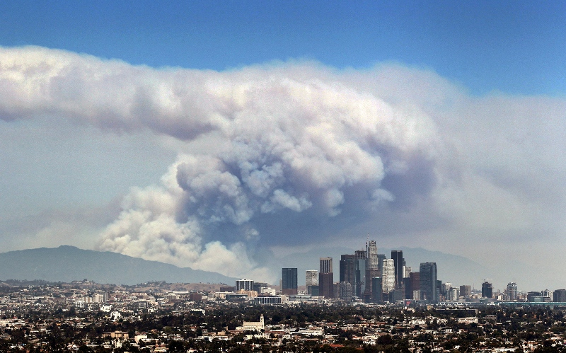 Smoke from wildfires burning in Angeles National Forest filled the sky behind the Los Angeles skyline on June 20, 2016.  Image courtesy of Ringo H.W. Chiu / AP.
